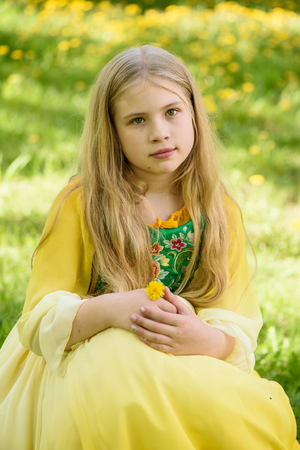 Blond young girl posing in a yellow green dress sitting on the grass with dandelions yellow flowers