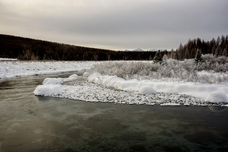 Winter landscape by a river in the sunset Imagens