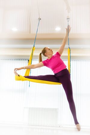 Fit pretty young woman wearing sportwear doing fly yoga stretching exercises in fitness training white gym loft classroom.