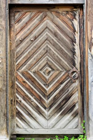 Old wooden door with the wooden carved architrave Standard-Bild