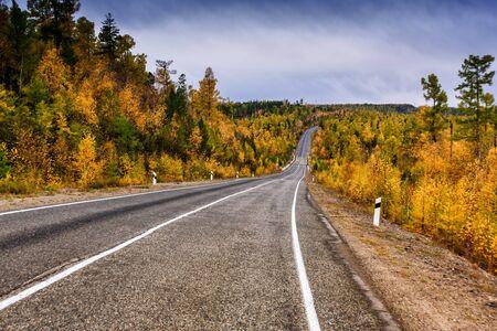Eine geschwungene Herbststraße mit bunten Wäldern und Bergen in der Ferne