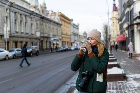 Meisje in winterkleren met camera en kaart in het historische centrum van de stad houdt een kopje koffie op straat