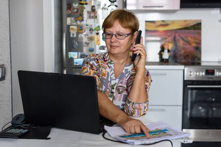 A 65-year-old woman works at home online by laptop and talks via phone because of the corona virus pandemic, more companies in are relying on the home office for their employees.