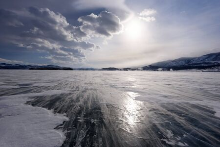 Beautiful clouds over the ice surface and windy snowdrift on a frosty day. Frozen Lake Baikal.