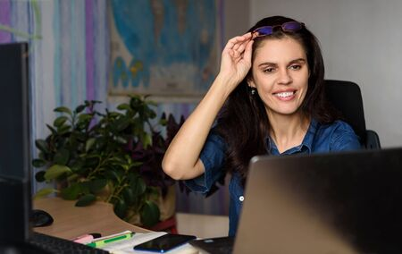 Smiling young woman in denim shirt works online with a laptop in the office at desk or at home, looks to the screen and holds glasses on her head with hand. World map in the background