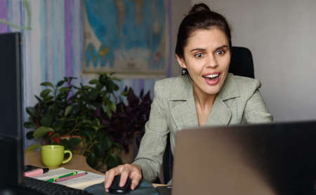 Shocked business woman using laptop looking at computer screen at home office. Human face expression, emotion, feeling, perception, body language, reaction