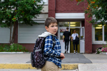 Child boy with bag stays near elementary school and looks to the camera
