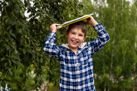 Funny smiling little boy plays with books. Back to school. Standard-Bild