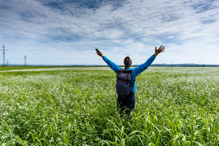 Women raises her hands and stays on a beautiful green meadow Standard-Bild