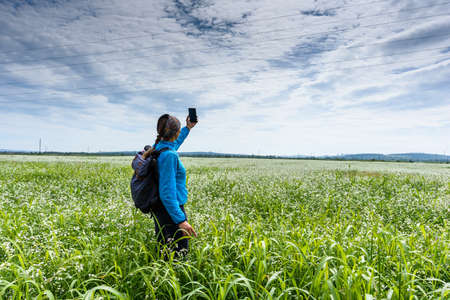 Girl holds phone, takes video call and stands on a beautiful green meadow