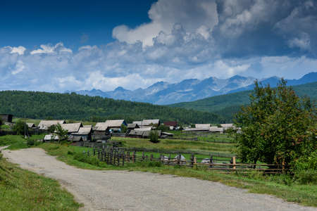 Old Russian village in Buryatia lying in the Tunkinskaya valley with mountain and clouds in summer day Standard-Bild
