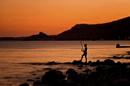 A boy fishing alone at sunset. Stock Photo