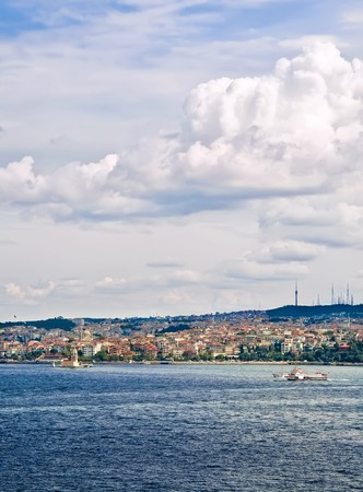 A view from Topkapi Palace, towards a famous landmark,The Maiden Tower, and a ferry boat passing by on a cloudy day. Stock Photo