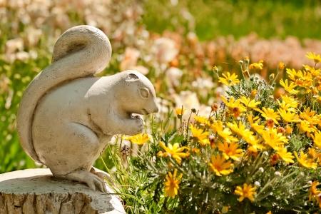 Un lindo Chipmunk Stone estatua de piedra en una configuración de jardín con flores