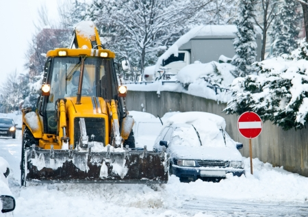 Yellow Bulldozer Snow Plowing Street In Urban Area photo