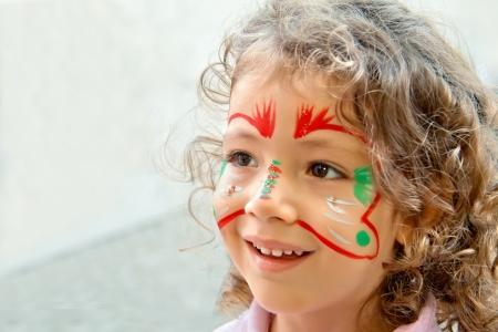 Een close up van het gezicht van een Turkse klein meisje geschilderd van een vlinder, op, fototoestel, op een festival in Istanbul. Stockfoto