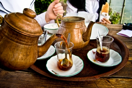 Drinking traditional Turkish Tea with Turkish tea cup and copper tea pot, and eating tost with friends. photo