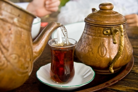 Drinking traditional Turkish Tea with Turkish tea cup and copper tea pot.