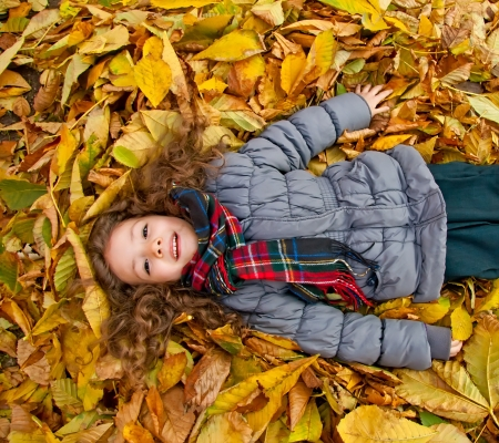 Little Girl Laying On A Heap Of Yellow Leaves Stock Photo - 16847469