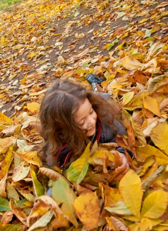 Little Girl Laying On A Heap Of Yellow Leaves photo