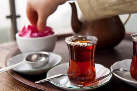 Drinking traditional Turkish Tea with Turkish tea cup and copper tea pot, and eating tost with friends.
