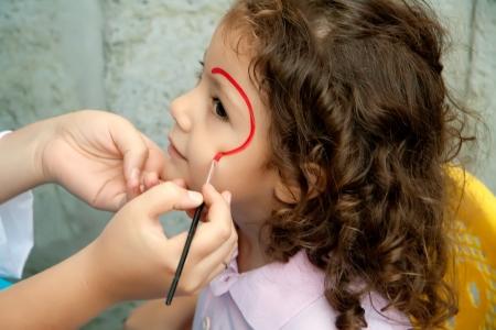 pintura en la cara: Cara de niña pintado por un artista en un festival Foto de archivo