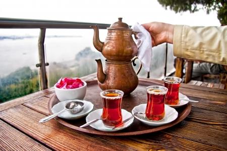 トルコの紅茶のカップと銅茶ポットで伝統的なトルコの紅茶を飲む