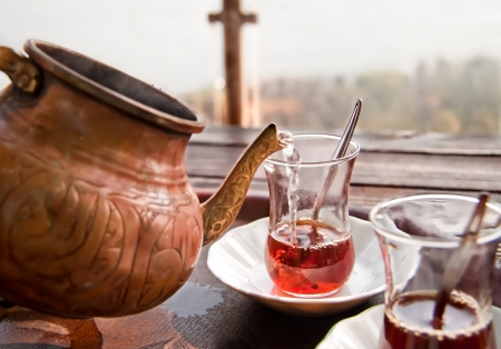Drinking traditional Turkish Tea with Turkish tea cup and copper tea pot Stock Photo