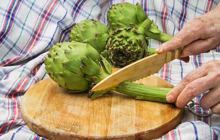Globe Artichoke On Cutting Board Being Cutted With a Bamboo Knife     photo