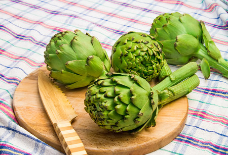 Globe Artichoke On Cutting Board With a Bamboo Knife photo