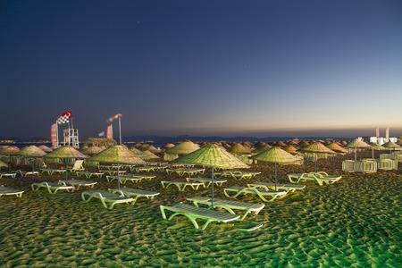 Beds and straw umbrellas on Sarimsakli Beach, Turkey At Night