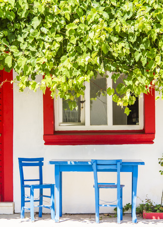 Blue Table With Chairs And A Red Door And Window At Bozcaada, Canakkale, Turkey