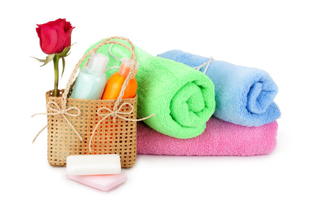 soft towels, soap, shampoo, cream arranged in a basket photo