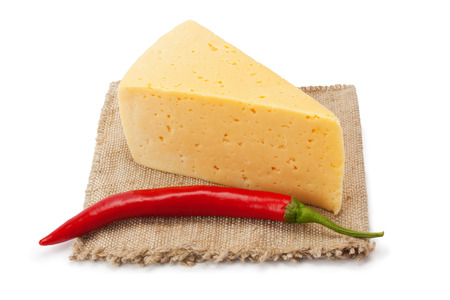 cheese and chili peppers on cloth isolated on white background photo