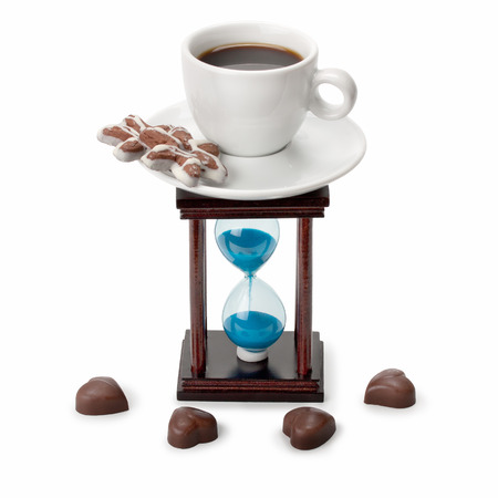 hourglass and a cup of coffee ,cookies ,chocolate candy isolated on white background photo
