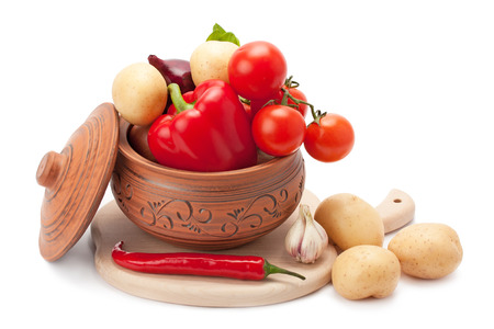 vegetables stacked in a clay pot isolated on white background photo