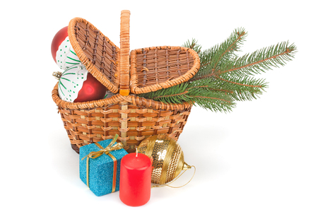 gift basket: fir branches with balls in the basket, candles and gift boxes isolated on white