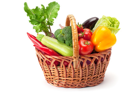 vegetables: fresh and ripe vegetables arranged in a basket isolated on white
