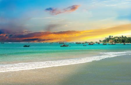 azul turqueza: Hermoso amanecer, arena blanca playa tropical, agua de mar turquesa. Barcos de pescadores en el agua. Las palmeras y vegetación tropical en la costa.