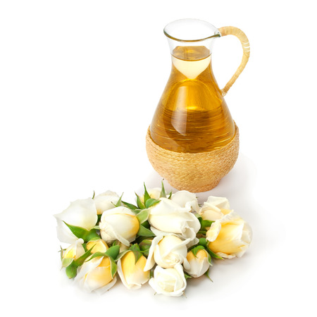 Attar: Rose flower and buds with aromatherapy essential oil glass bottle isolated over white background.