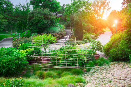 landscaped garden: Winding road in a peaceful landscaped garden in the morning sun. Stock Photo