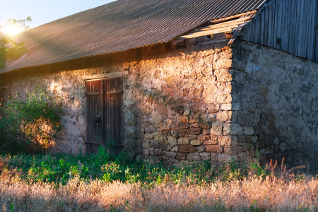 Closed wooden door in a stone wall of an old barn. Stock Photo