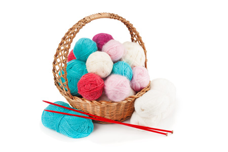 Yarn balls and knitting needles in basket isolated on white background.