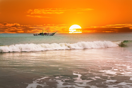 Beautiful sunrise, tropical beach white sand, turquoise ocean water . Boats of fishermen on the water.