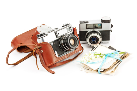 Vintage film photo-camera in leather case and old photos isolated on white background.