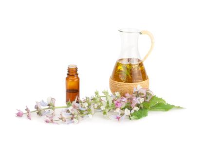 Essentiële olie van salie en bloemen op een witte achtergrond. Stockfoto
