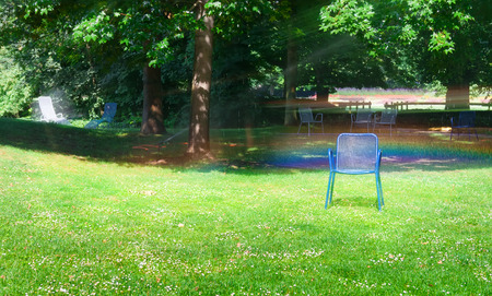 Summer park and a rainbow from splashing water automatic irrigation. Stock Photo