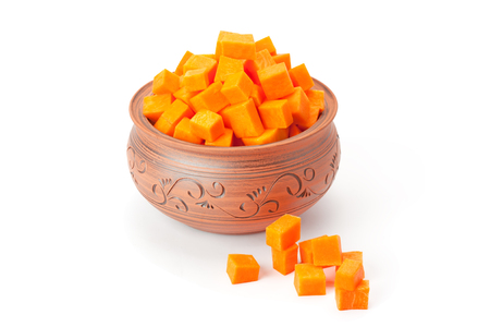 energy healing: pumpkin cubes in a clay pot isolated on white background