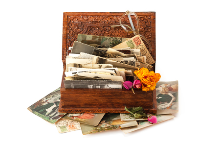 Old family photos stacked in wooden box isolated on white