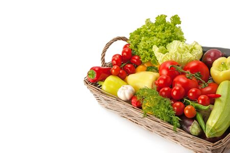 Fresh and ripe vegetables arranged in a basket isolated on white. Healthy vegan food. Photo with free space for text. Archivio Fotografico
